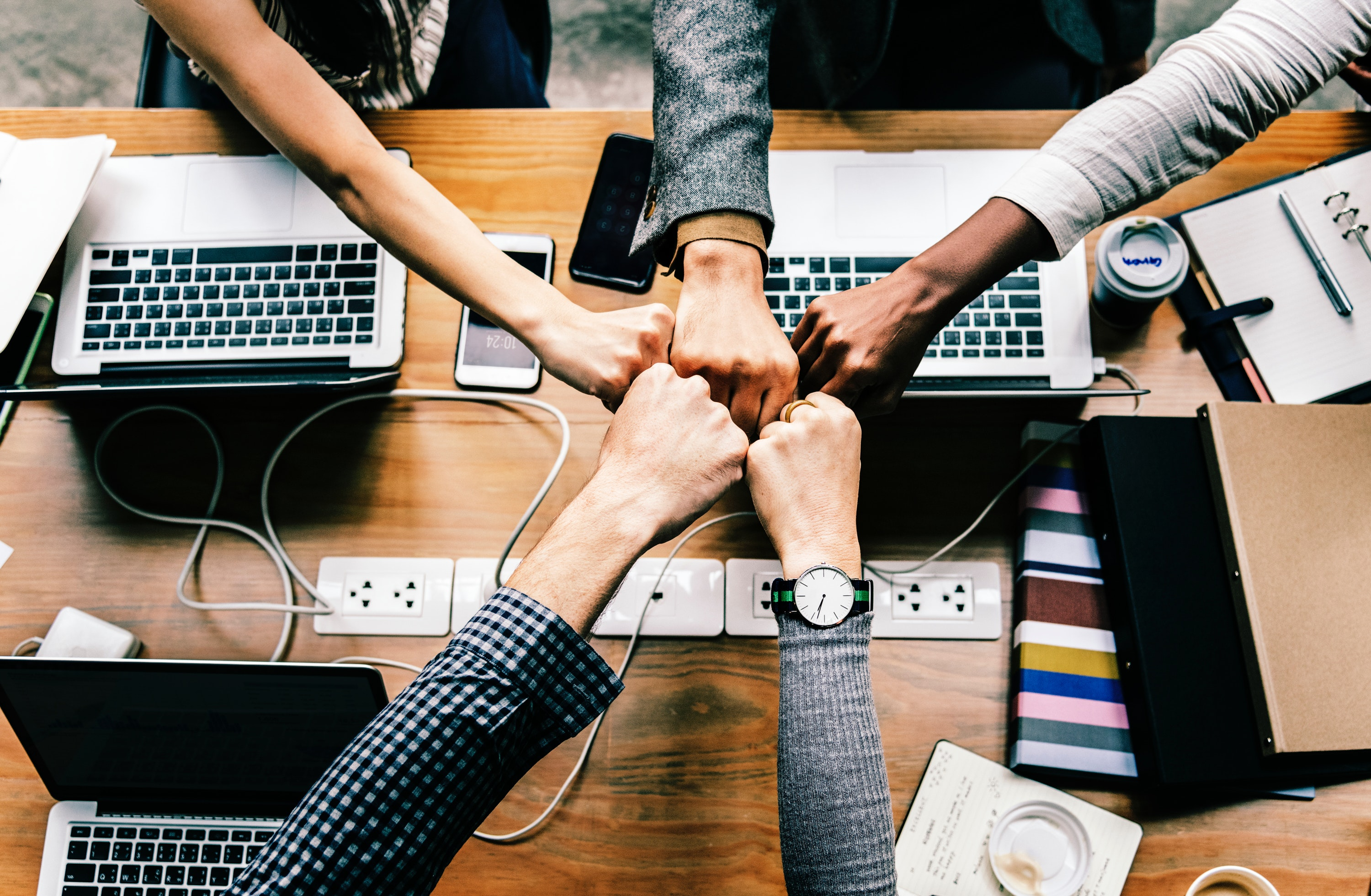 group of coworkers putting their fists together in a show of unity amidst their growing culture