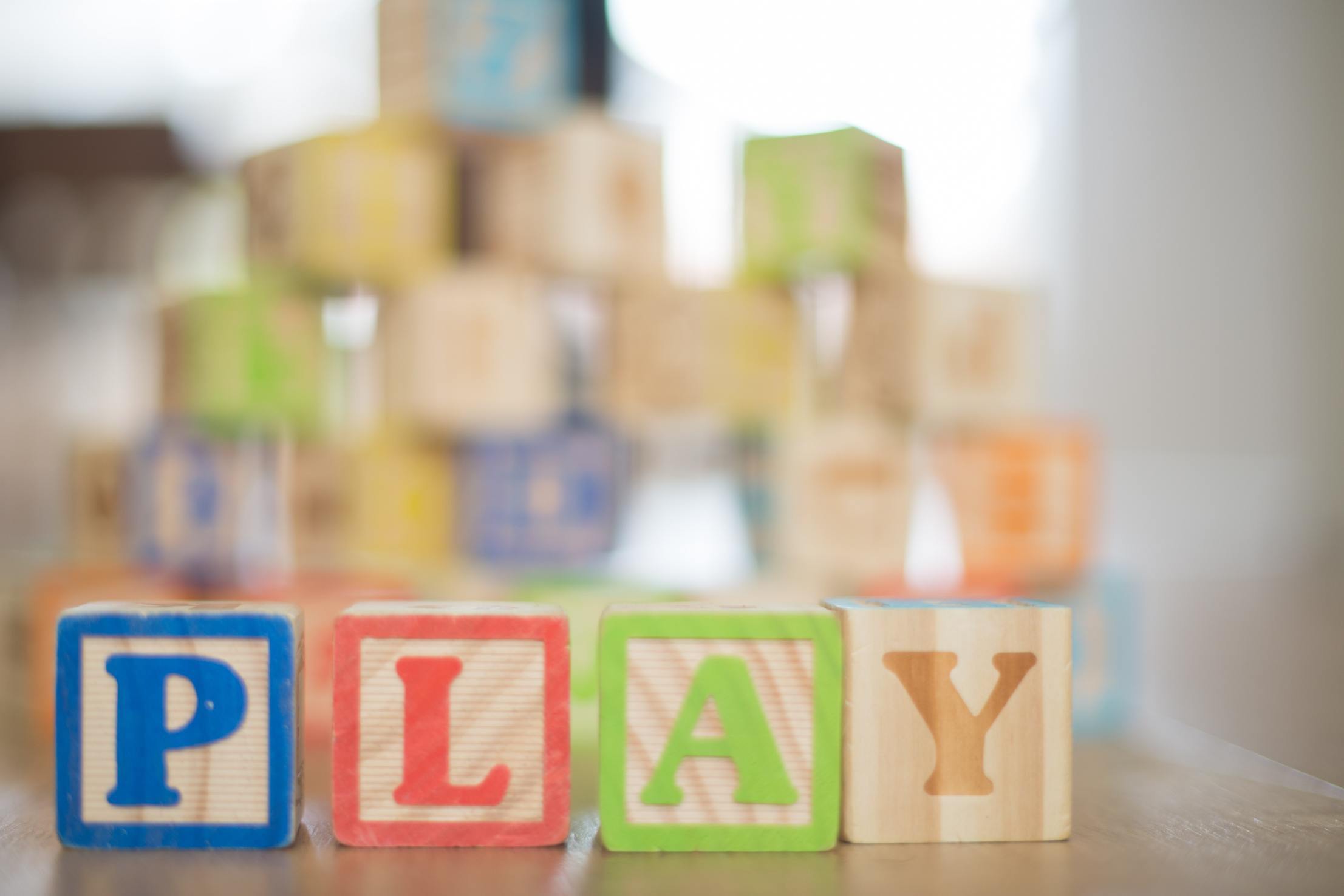 Photo of colorful wooden blocks that spell out play.