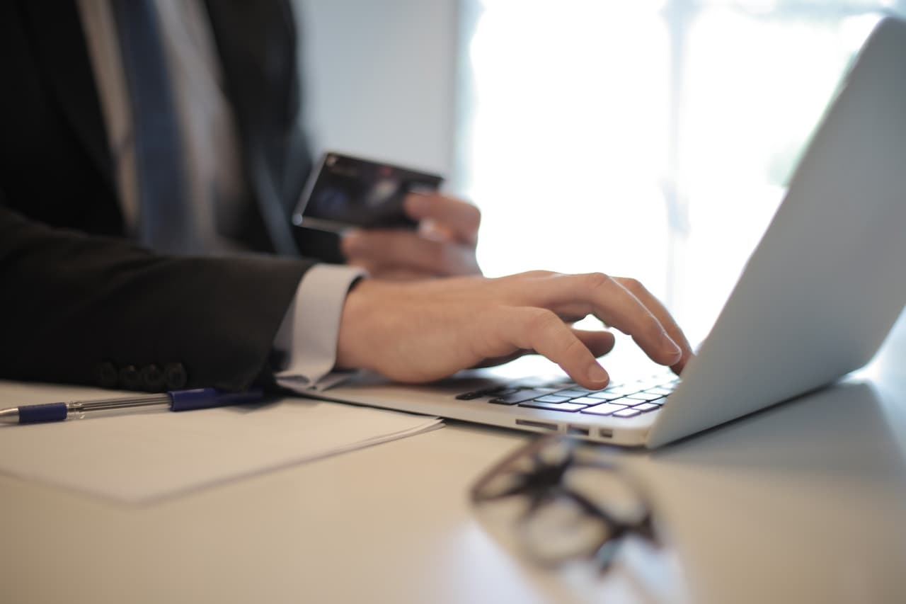 Business person sitting at a desk and making a purchase.