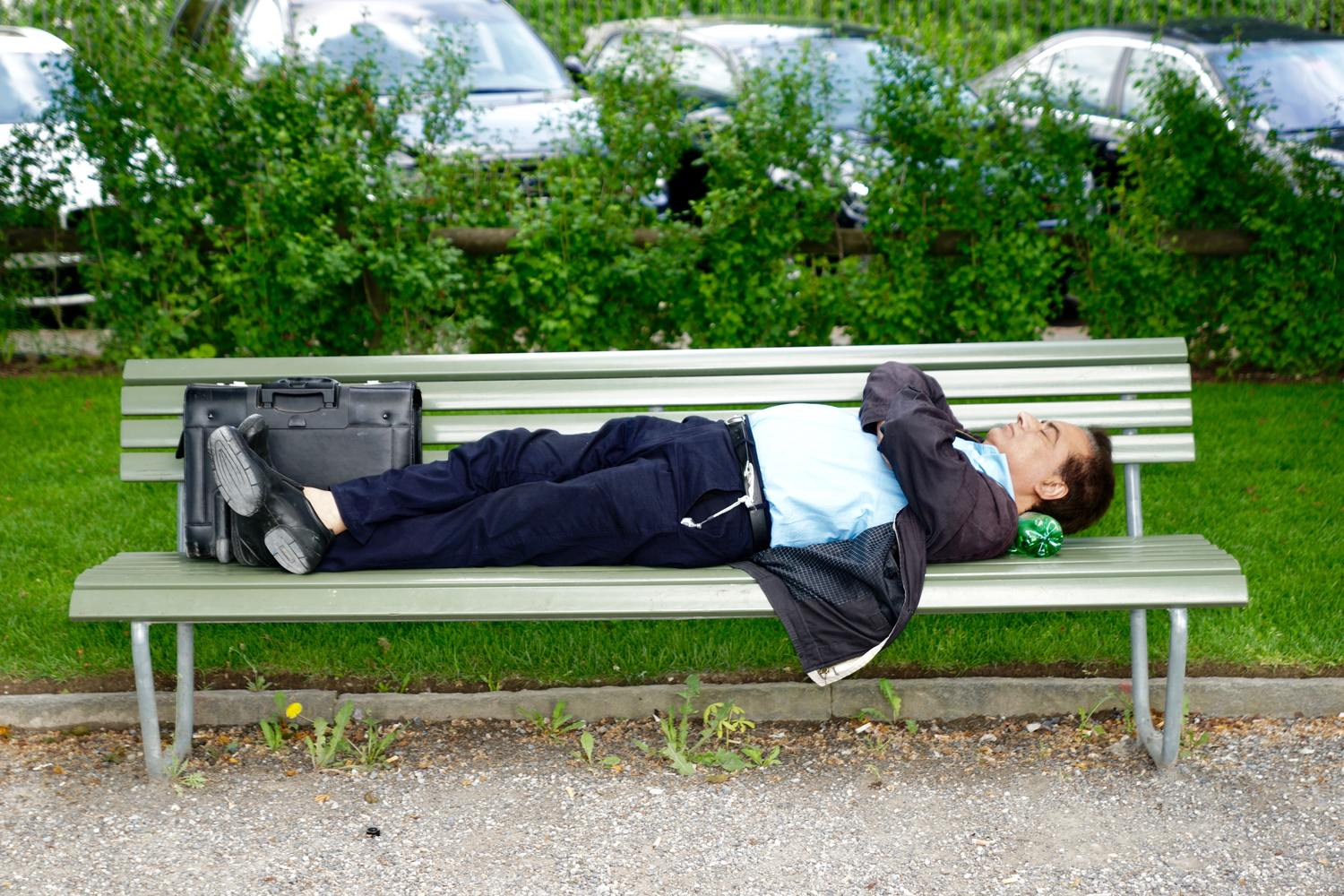 Photo of a businessman taking a nap on a bench in order to boost his productivity.