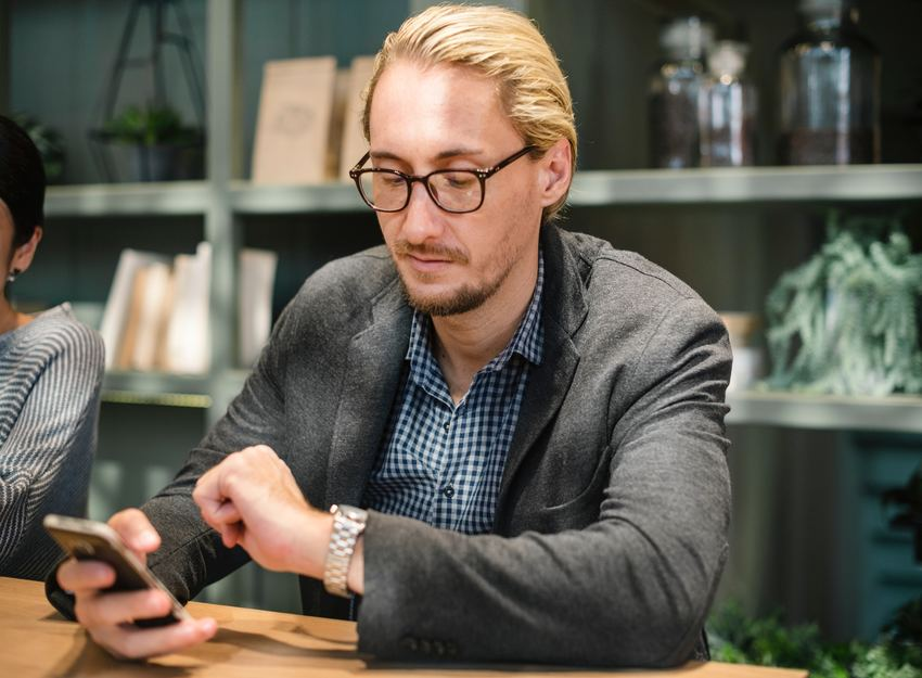 photo of a man sitting at a desk while holding his phone and checking his watch