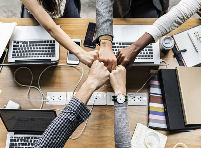 Photo of several people sitting around a desk and putting their fists together as representation of their dedication to continuous improvement.