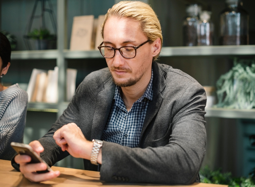 photo of a man sitting down while holding his phone and checking the time on his watch