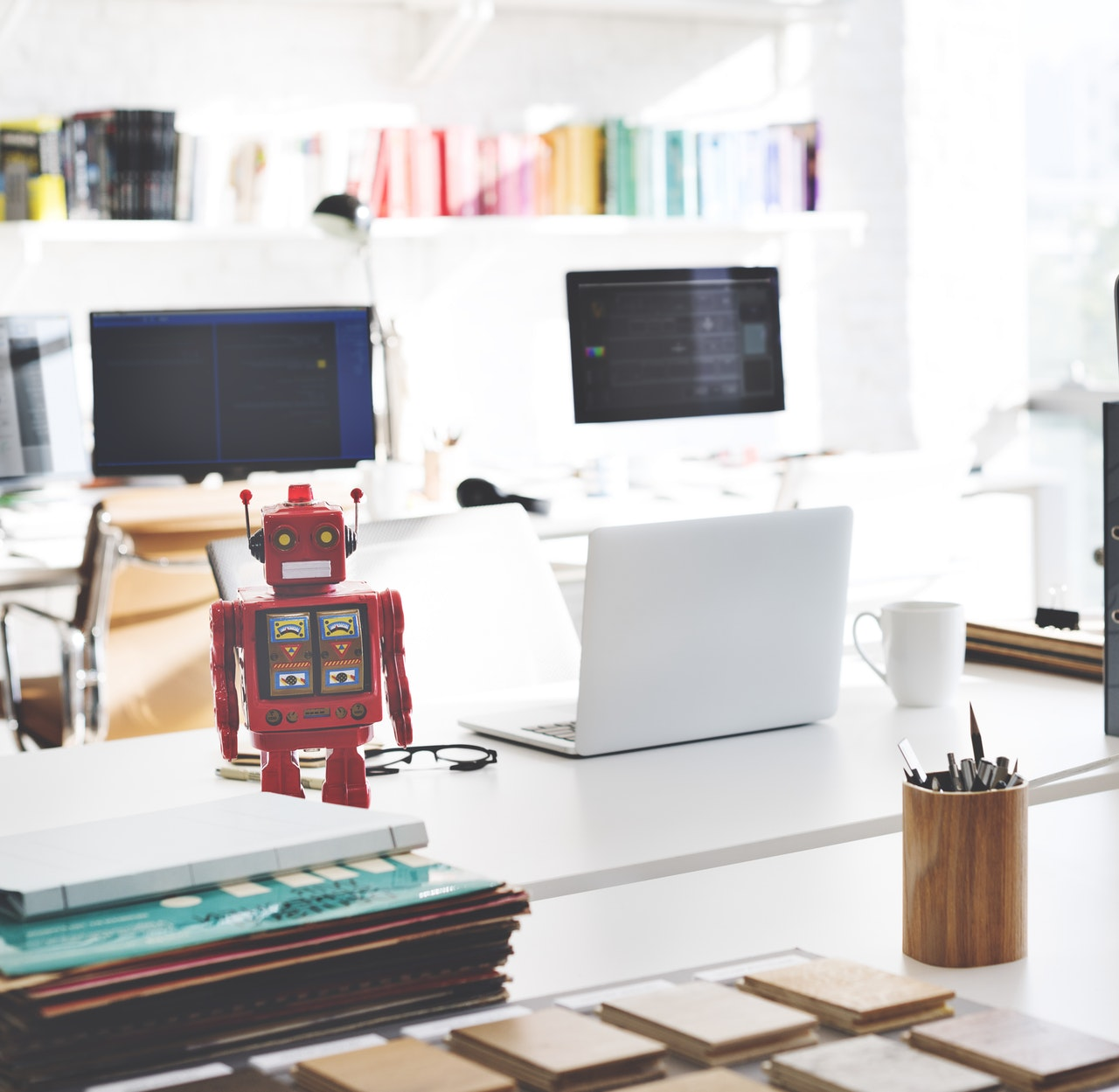 photo of a desk with two laptops and a robot to represent artificial intelligence