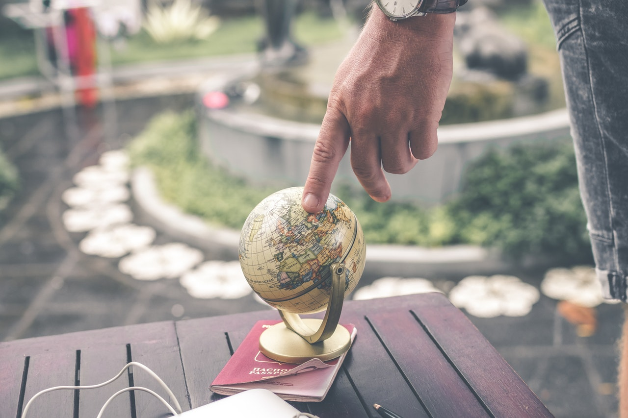 photo of a man putting his finger on a small, wooden globe.