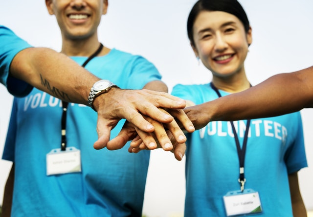 photo of people with their hands together and wearing t-shirts that say volunteer