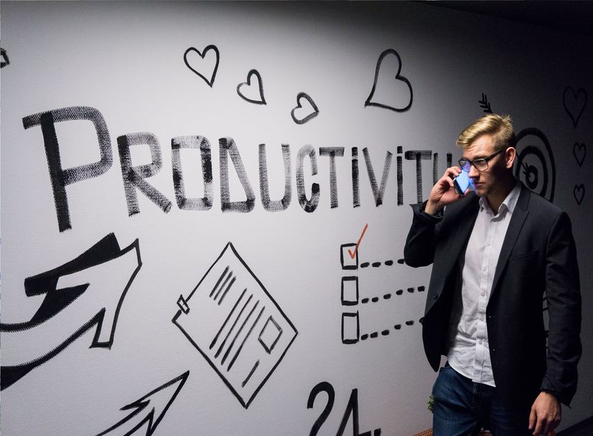 photo of a man talking on his phone while walking past a wall that says productivity and has some arrows and a checklist graphic on it