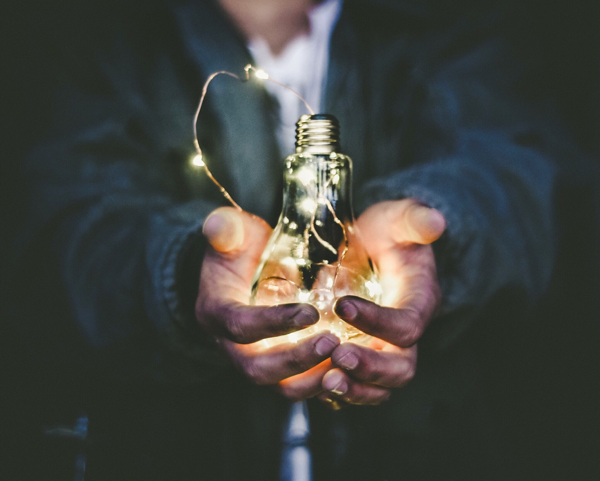 Photo of a business man holding glowing lightbulb that symbolizes the incredible potential that delegative leadership has.